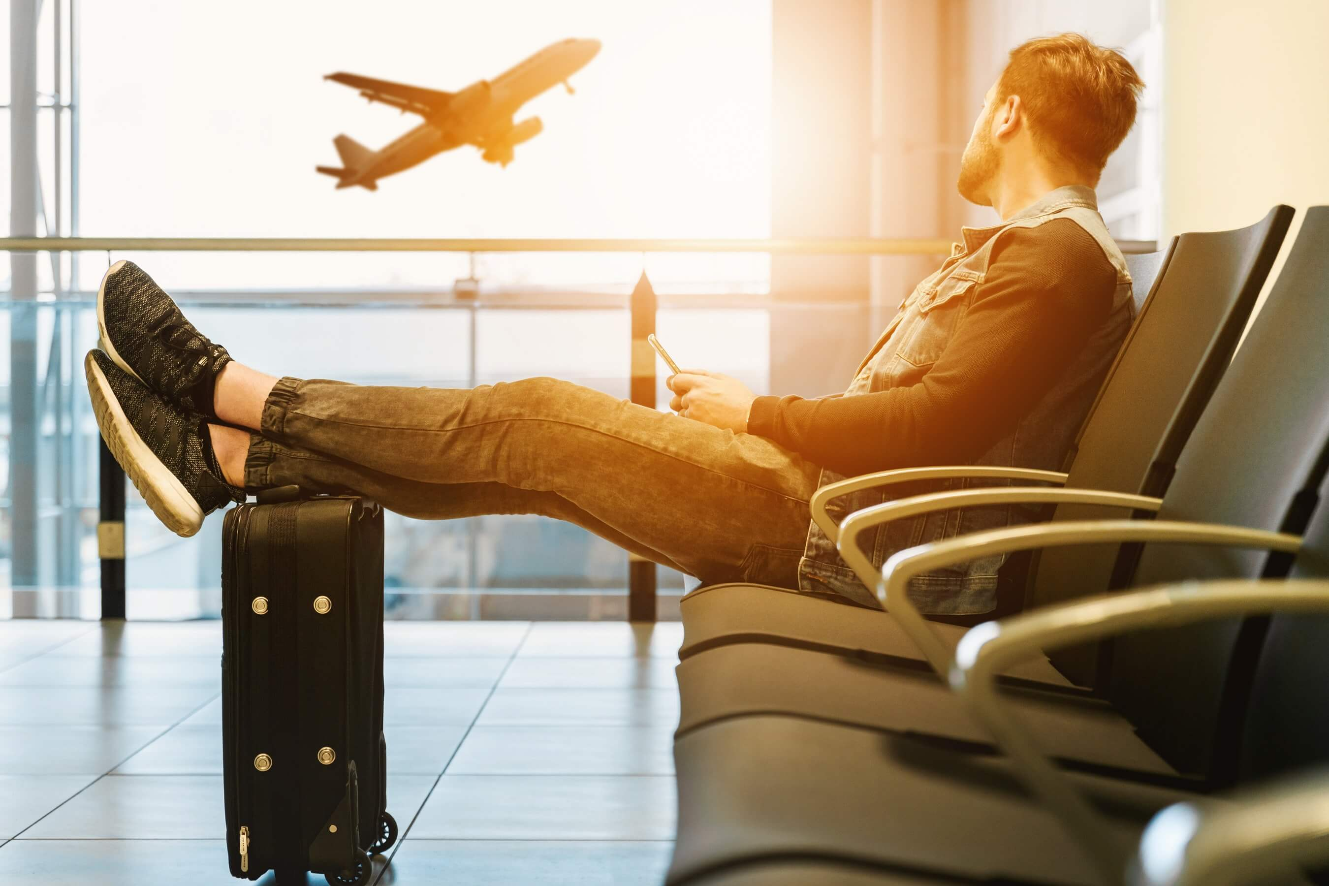 Bemannen Sie den sitzenden Flughafen, der mit den Telefonfüßen wartet, die auf Gepäcktasche gekreuzt werden
